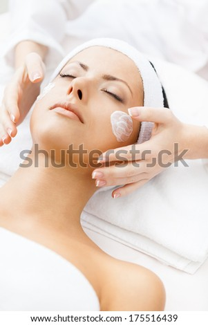 Hands of therapist apply cream to face of woman. Concept of care and youth - stock photo