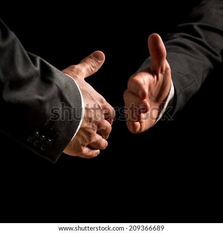 Hands of two businessmen reaching out in a business handshake with receding perspective on a dark shadowy background conceptual of a deal, partnership, agreement, congratulations or greeting. - stock photo