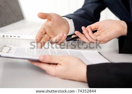 Hands of two businesspeople discussing a contract - stock photo