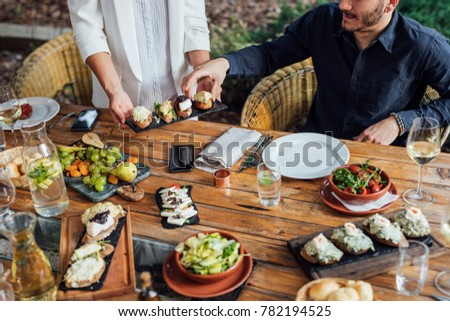 Hands of unrecognisable woman putting a plate with vegetarian meal on dining table at backyard celebration.