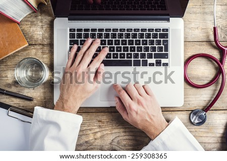 Hands of unrecognizable doctor writing on a computer. Wooden desk background. - stock photo