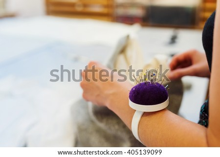Hands of unrecognizable tailor woman with pin cushion working - stock photo