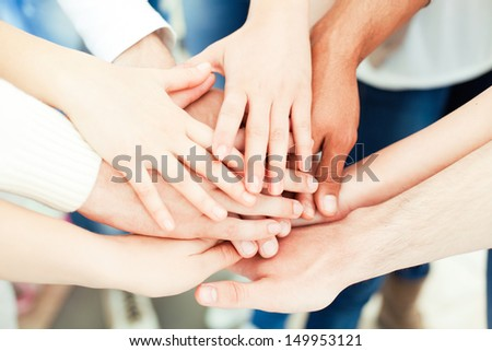 Hands of various people one on top of the other. - stock photo