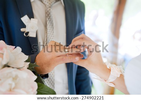 Hands of wedding couple putting golden rings to finger of each other. - stock photo