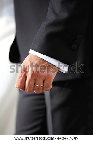 Hands of wedding groom and he has wedding ring in his hand.