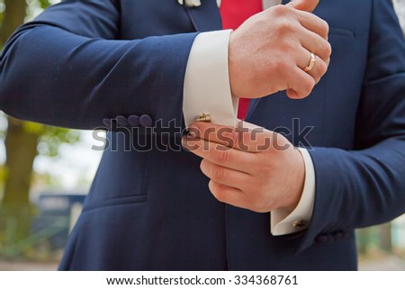 Hands of wedding groom getting ready in suit. Background - stock photo