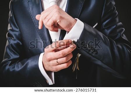 Hands of wedding groom getting ready in suit. black studio background. - stock photo
