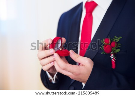 Hands of wedding groom getting ready in suit. The groom holds the box with the wedding rings. - stock photo