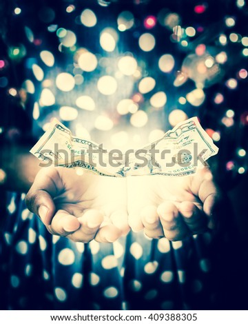 Hands of witch in a dark room conjuring a spell with US Dollar note is floating on her hands - stock photo