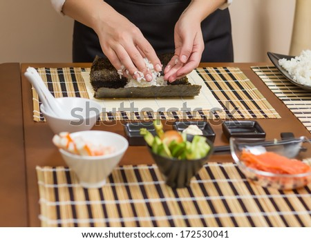 Hands of woman chef filling japanese sushi rolls with rice on a nori seaweed sheet. Selective focus in sushi roll. - stock photo