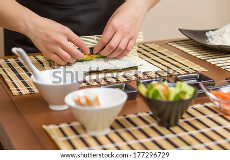 Hands of woman chef rolling up a japanese sushi with rice, avocado and shrimps on nori seaweed sheet