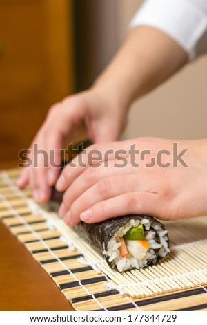Hands of woman chef rolling up a japanese sushi with rice, avocado and shrimps on nori seaweed sheet - stock photo