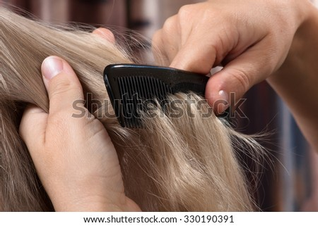 hands of woman combing hair her daughter