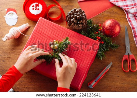 Hands of woman decorating Christmas gift box - stock photo
