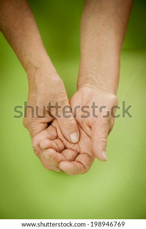 Hands Of Woman Deformed From Rheumatoid Arthritis. Green background