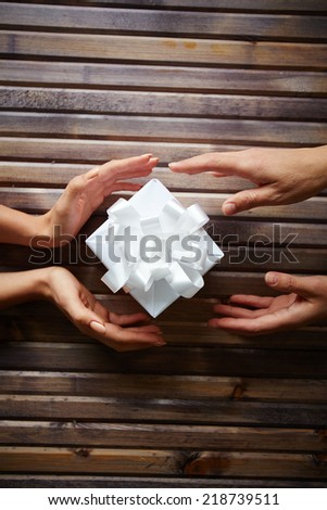 Hands of woman giving Christmas present to her friend - stock photo