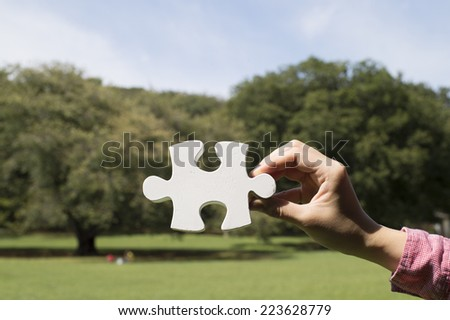Hands of woman has a piece of white puzzle