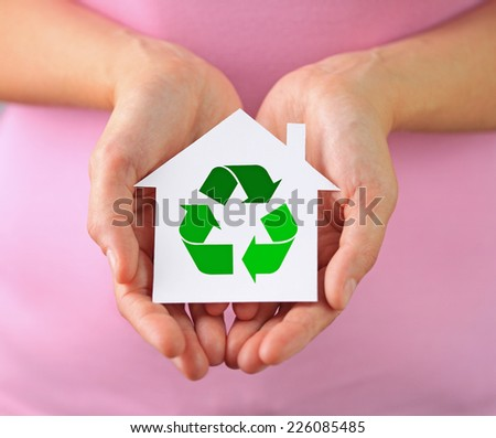 Hands of woman holding paper house with recycling symbol - stock photo