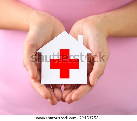 Hands of woman holding paper house with red cross - stock photo