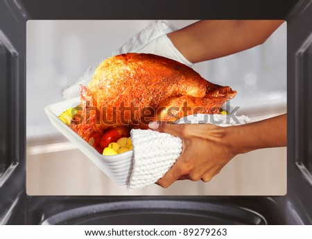 hands of woman is taking out  turkey with potato from oven - stock photo