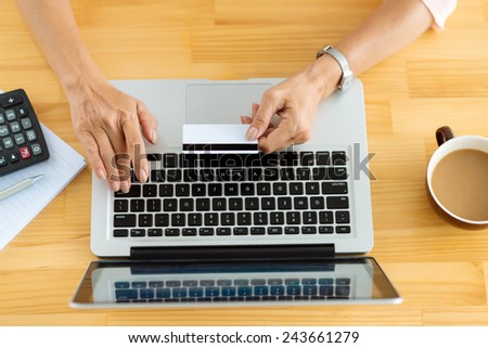 Hands of woman paying for her online purchases by credit card, view from above - stock photo