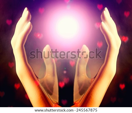 Hands of woman praying to the light,heart bokeh background - stock photo