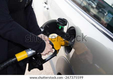Hands of woman refueling her car at the gas station
