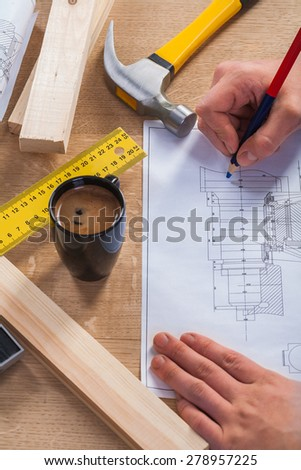 hands of worker with pencil and blueprint on wooden table with coffee cup  claw hammer ruler  - stock photo