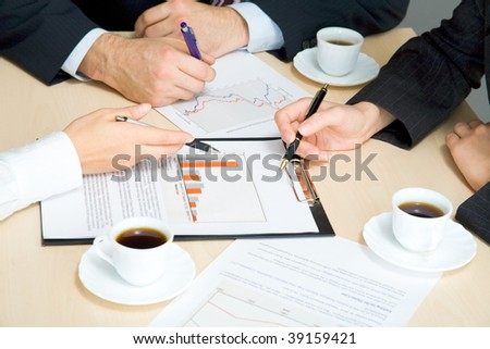 Hands of working businesspeople at meeting - stock photo