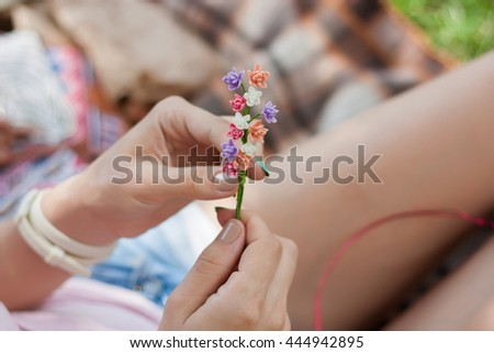 Hands of Young girl sitting in the park and crafting a crown from colorful artificial flowers, hand made summer concept