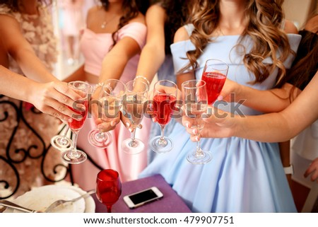 Hands of young girls decorated with manicure holding glasses filled with champagne at a party