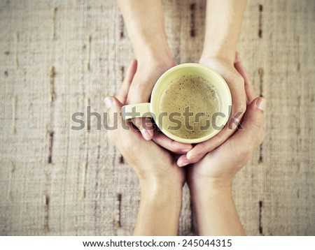 hands of young lovers holding a cup of coffee. - stock photo