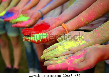 Hands of young people with Indian dyes on Holi color festival - stock photo