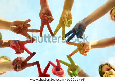 Hands of young people with Indian dyes on Holi color festival on blue sky background - stock photo