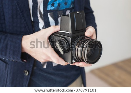 Hands of young photographer holding old medium format camera