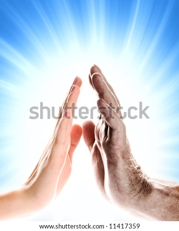 Hands of young woman and elderly man over abstract blue background - stock photo
