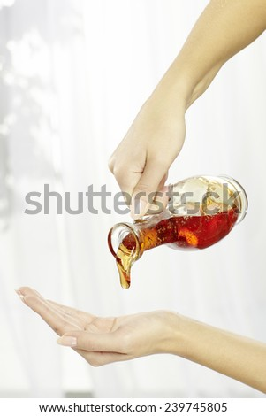 Hands of young woman holding essential oil