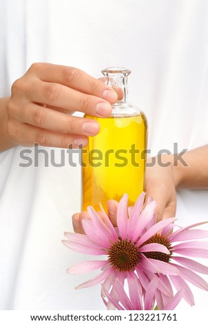 Hands of young woman holding essential oil and fresh coneflowers