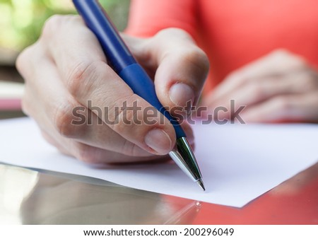 Hands of young woman signing paper.