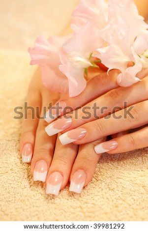 Hands of young woman with french manicure on the towel - stock photo