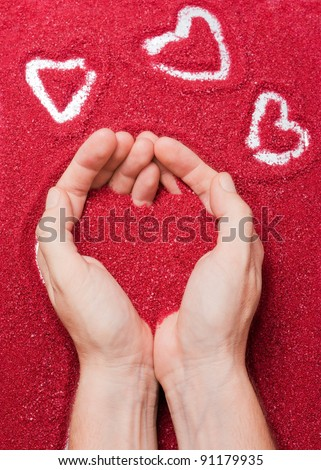 Hands offering a red sand heart