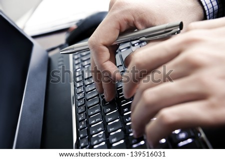 Hands on a laptop keyboard - a journalist, writer or a programmer at work - stock photo