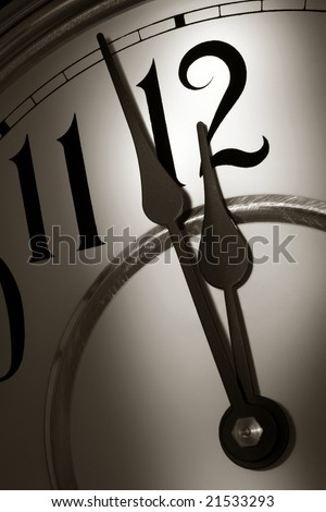 Hands on a traditional clock showing time two minutes before the stroke of midnight hour in dramatic scary light - stock photo