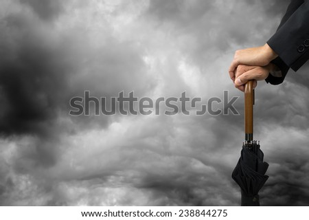 hands on an umbrella with a stormy sky horizontal - stock photo