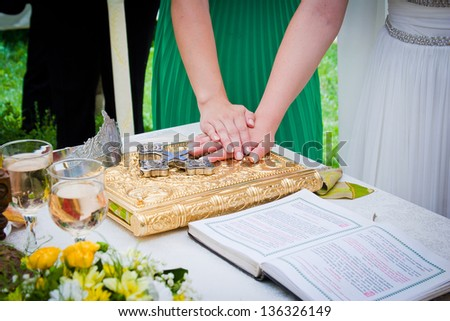 Hands on bible at a wedding ceremony - stock photo