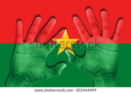 hands on Burkina Faso flag background - stock photo