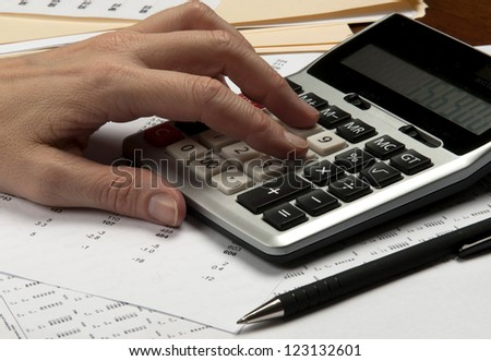 Hands on calculator  with pen and financial papers - stock photo