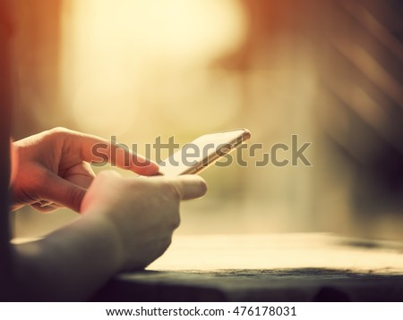 Hands on cell phone in bright sunlight