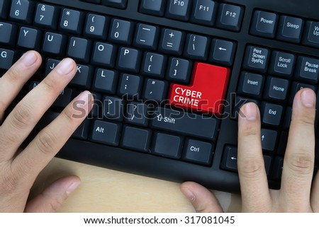"Hands on computer keyboard with ""Cyber Crime"" words at enter button. - stock photo"