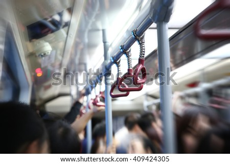 Hands on hand grips in subway coach - stock photo
